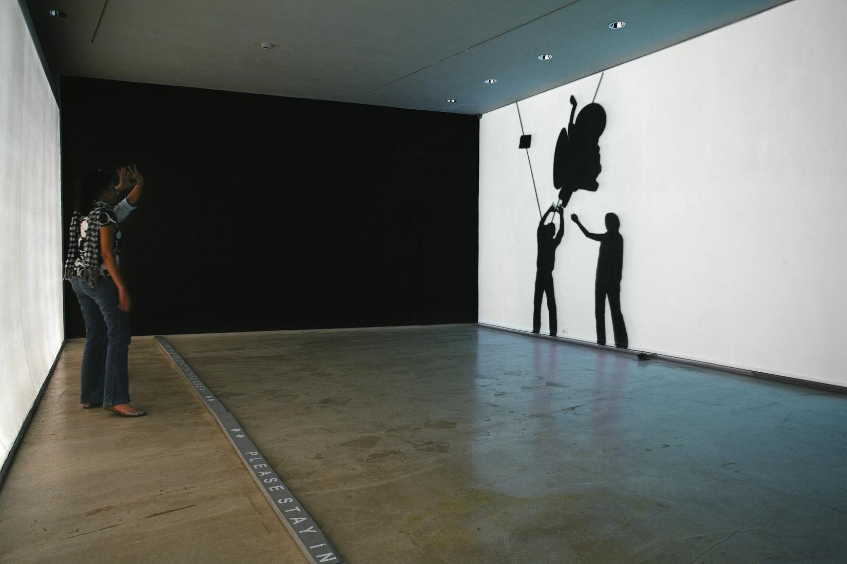 Photo: two people stand in a gallery facing a whit...