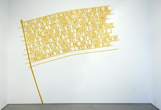 Photo of gold words on a white wall in the shape o...