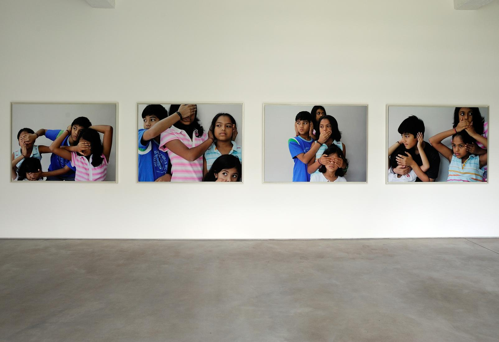 Four large photos installed on a gallery wall: fou...