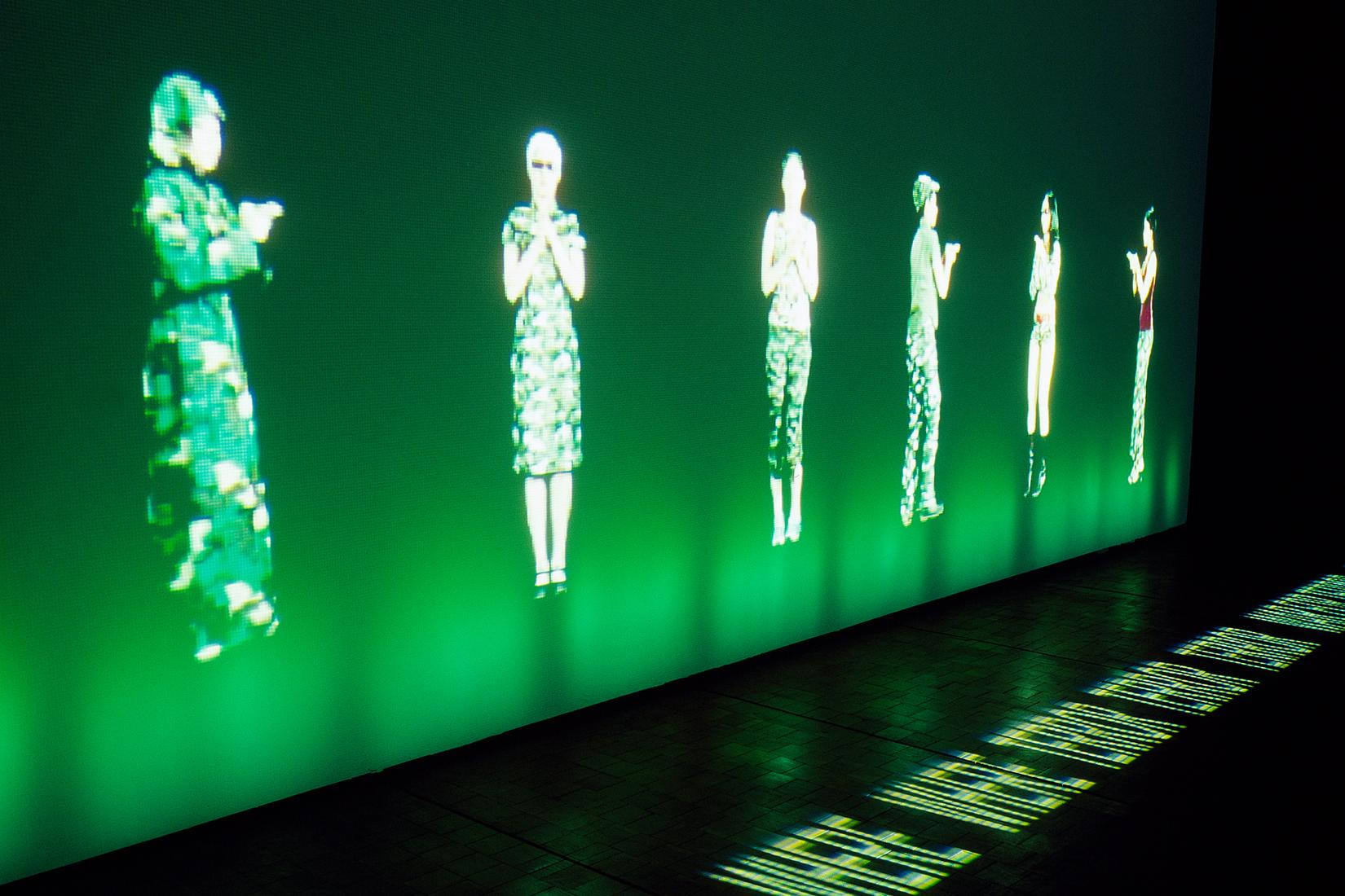 Photo: projection of a pixelated people on a brigh...