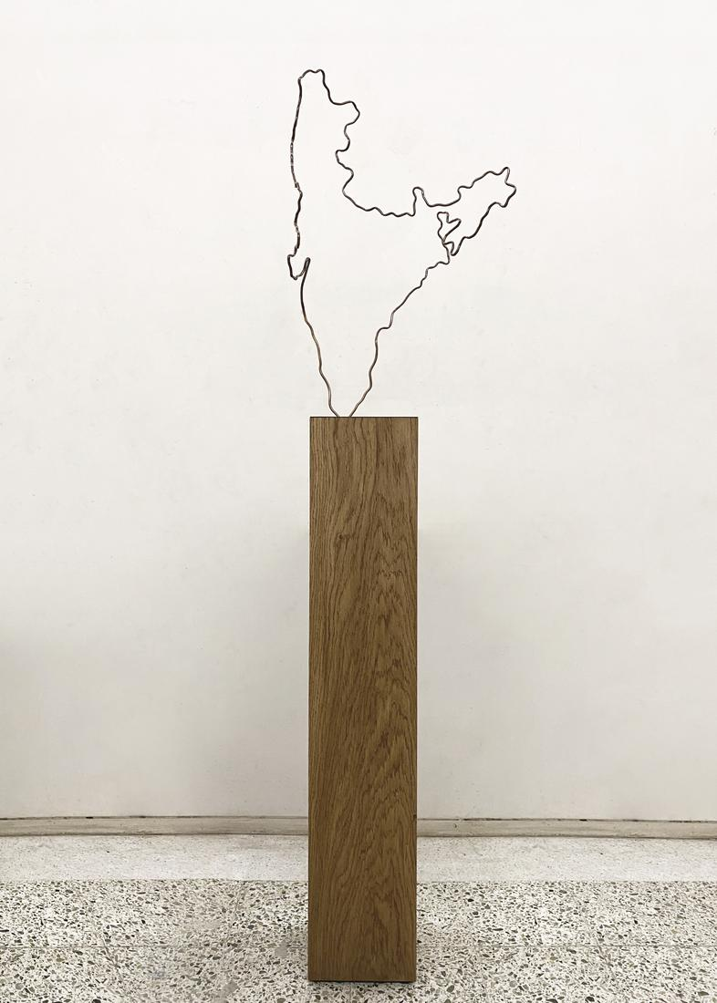 Thin wire outline of India on a tall wooden pedest...