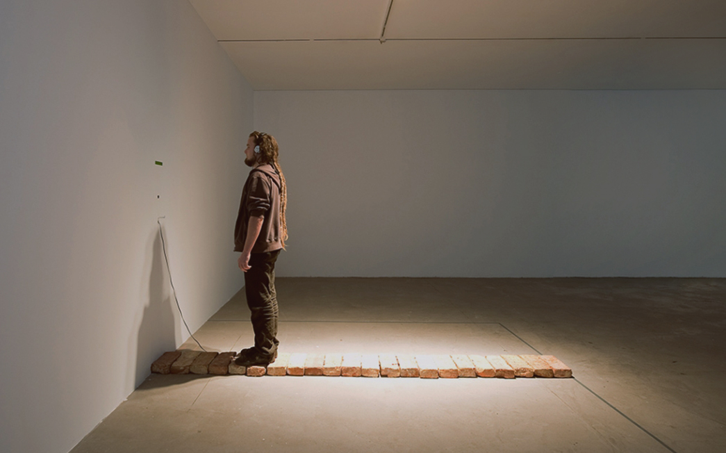 Installation photo. Man in a gallery stands on a r...