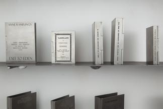 Engraved silver book covers on a metal shelf: Exit...