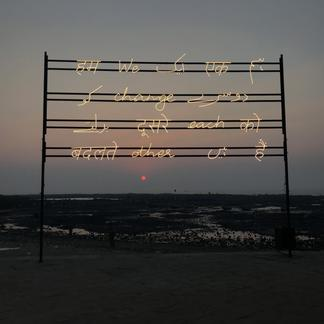 White cursive lights on a black metal rack with a...