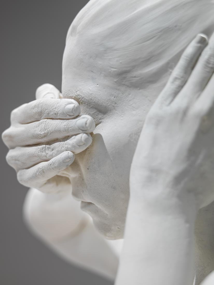Close up photo of sculpture of a woman covering he...