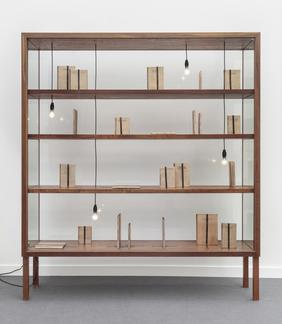 Glass vitrine with wooden shelfs displays beige bo...